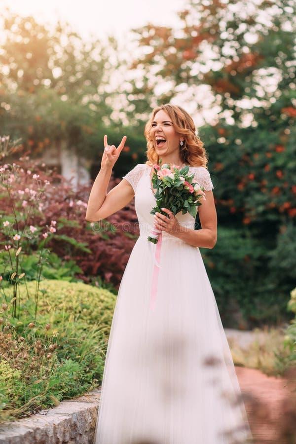 Den unga blonda flickan i en elegant lång vit ljus klänning skojar att skratta på kameran i en grön trädgård som rymmer royaltyfri fotografi