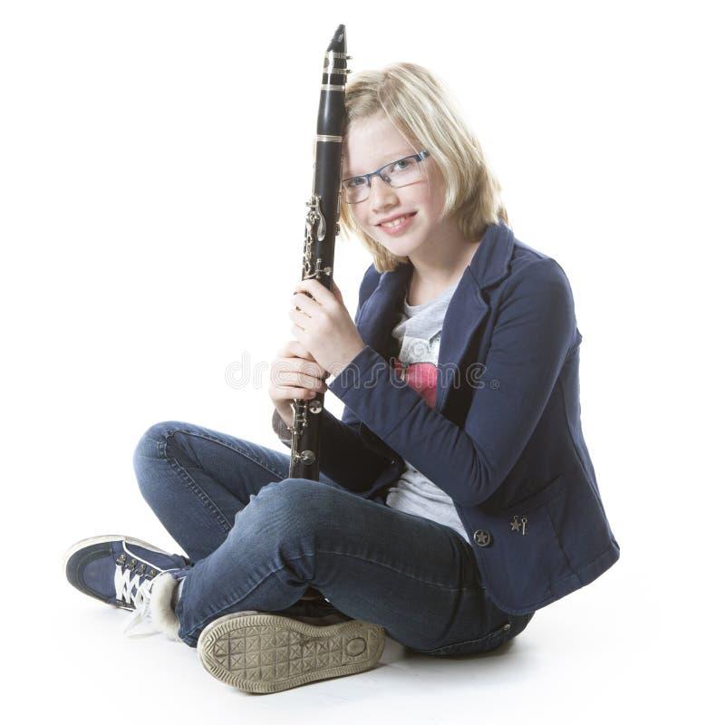Den unga blonda flickan sitter och rymmer klarinetten i studio royaltyfri foto