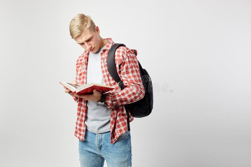 Den unga blonda grabben med den svarta ryggsäcken på hans iklädda skuldra en vit t-skjorta, en röd rutig skjorta och en jeans läs royaltyfri bild