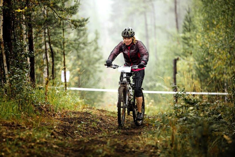 Den unga blonda kvinnacyklisten rider längs en skogslinga royaltyfria bilder