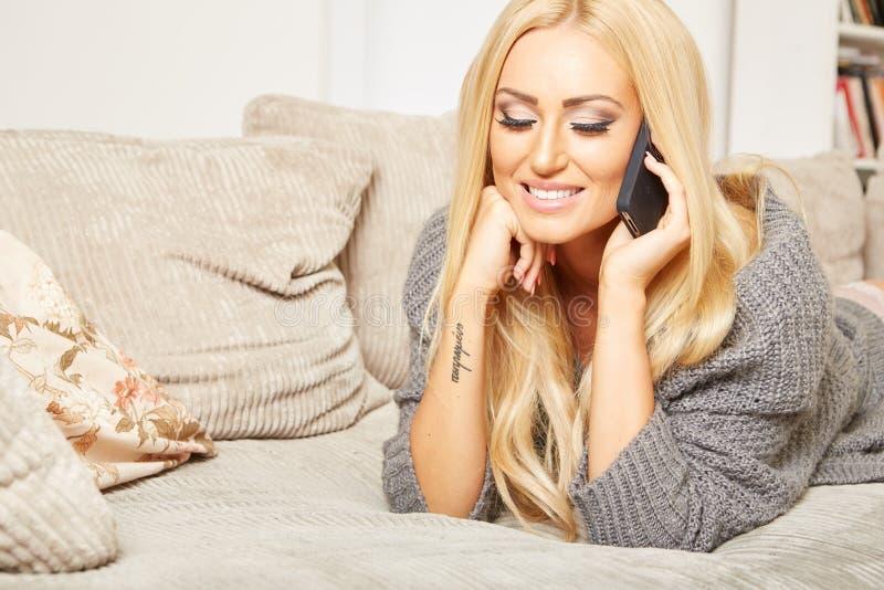 Den unga blonda kvinnan är avslappnande på en soffa royaltyfri fotografi