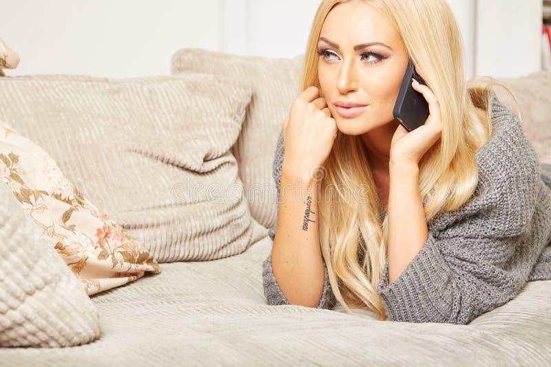 Den unga blonda kvinnan är avslappnande på en soffa arkivbild