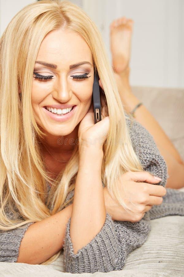Den unga blonda kvinnan är avslappnande på en soffa arkivfoto