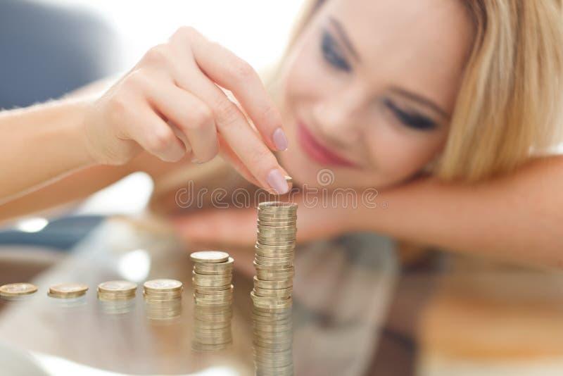 Den unga blonda kvinnan bygger pengarkolonner royaltyfri fotografi