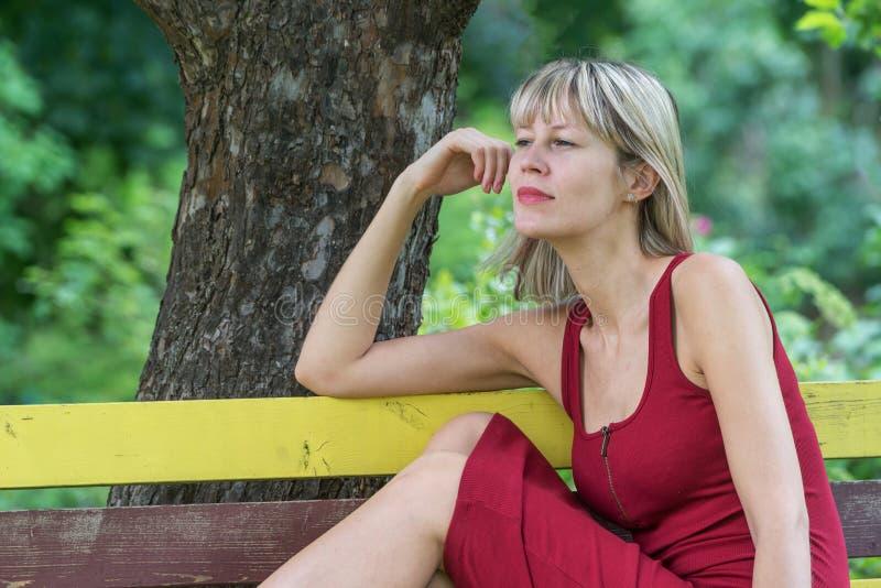 Den unga blonda kvinnan i en röd klänningbenägenhet sitter på en träbänk royaltyfria bilder