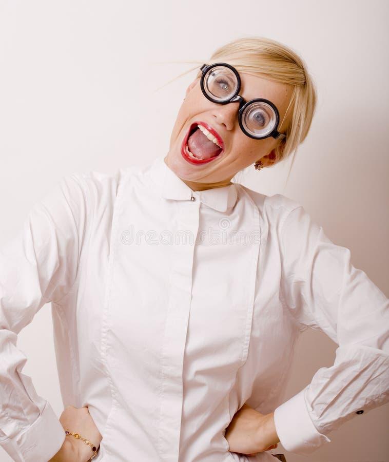 Den unga blonda kvinnan i exponeringsglas gillar bokmalen arkivfoto