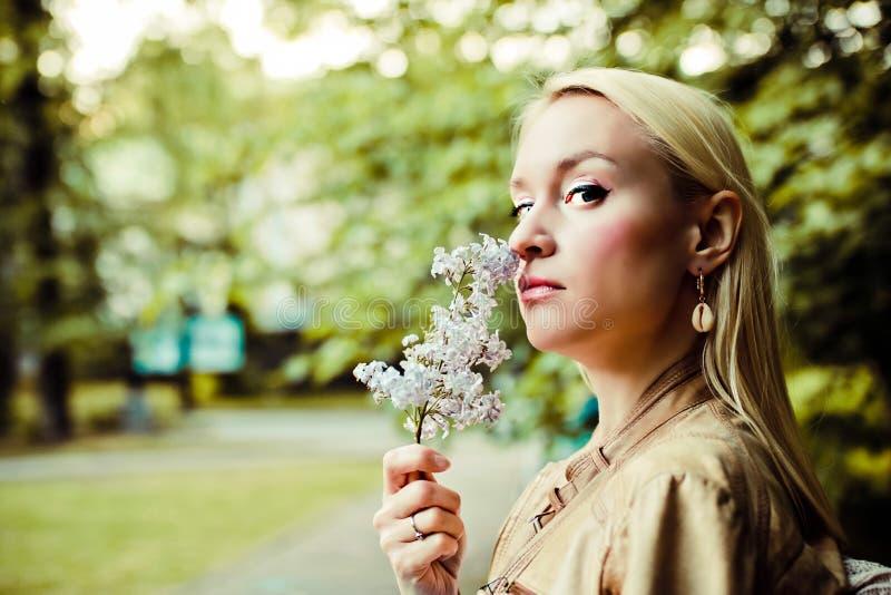 Den unga blonda kvinnan inhalerar doften av blommor och blickar på dig royaltyfri fotografi