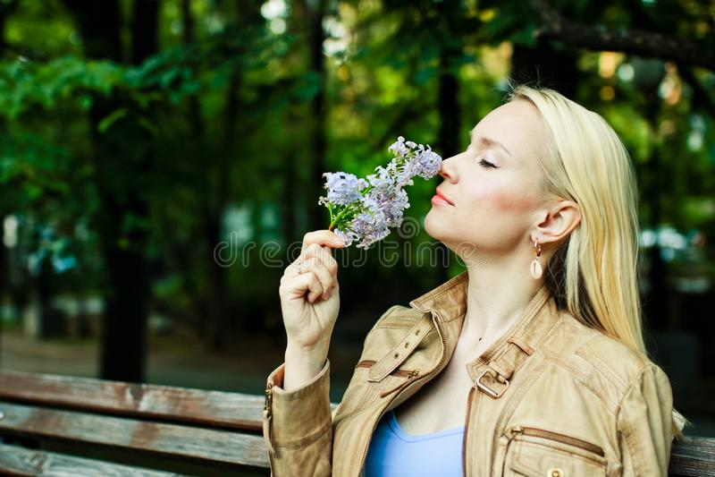 Den unga blonda kvinnan inhalerar doften av blommor parkerar på våren royaltyfri fotografi