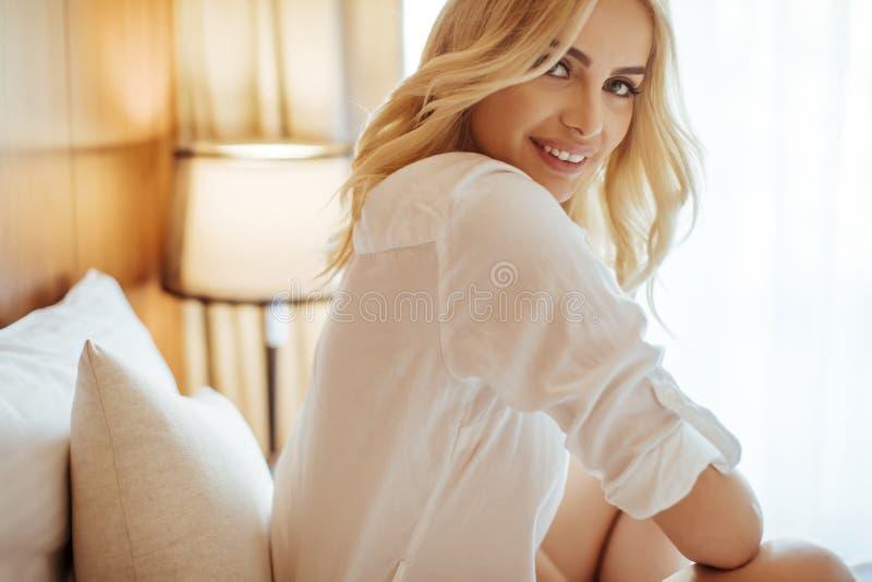 Den unga blonda kvinnan på sängen ser lycklig och tillfredsställd royaltyfria foton