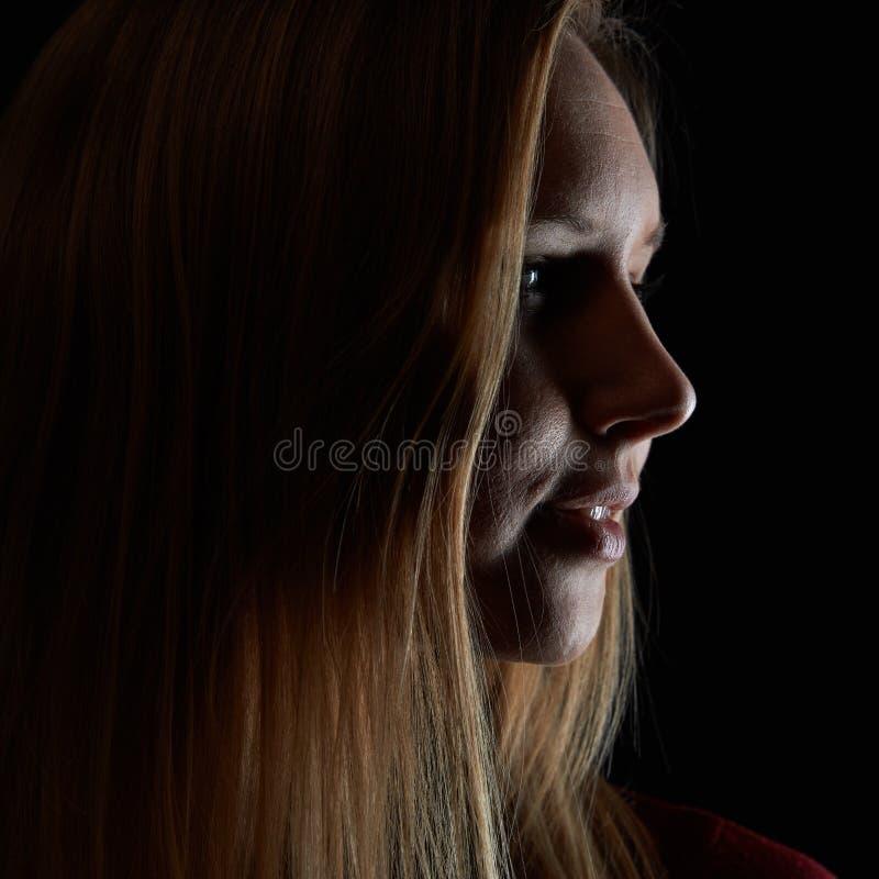 Den unga blonda kvinnan ser från sidan i mörkret royaltyfri bild