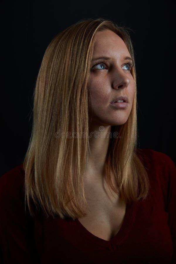 Den unga blonda kvinnan ser upp förhoppningsvis royaltyfria bilder