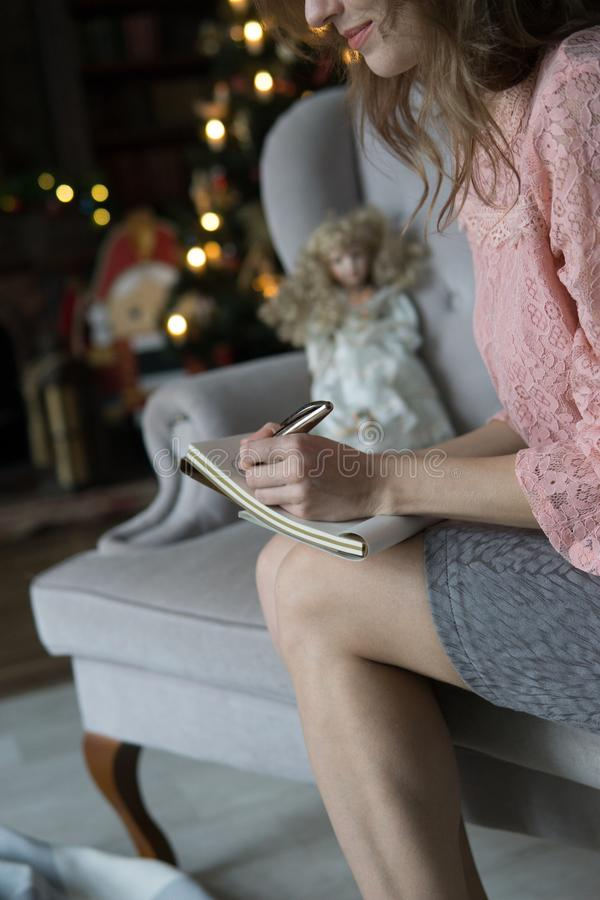 Den unga blonda kvinnan sitter på en grå soffa i en rosa blus och skriver med hennes vänstra hand med en penna i en anteckningsbo royaltyfria foton