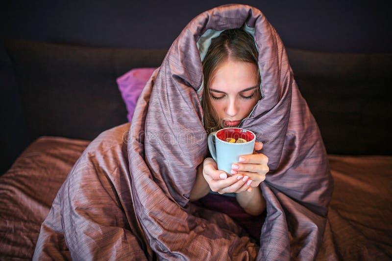 Den unga blonda kvinnan sitter på säng med det dolda huvudet Hon dricker varmt te från koppen Kvinnan rymmer det med båda händer  fotografering för bildbyråer
