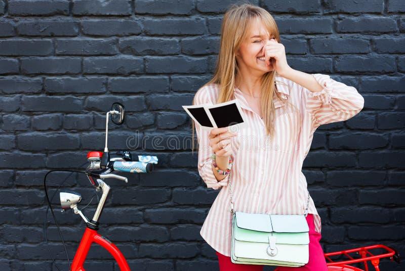Den unga blonda kvinnan skrattar, medan se foto arkivbild