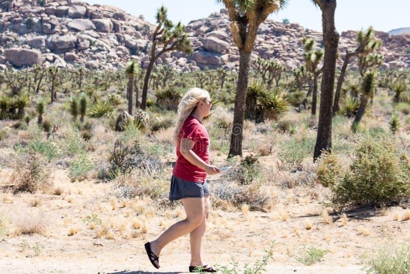 Den unga blonda vuxna kvinnan fotvandrar nära en skog av Joshua Trees fotografering för bildbyråer