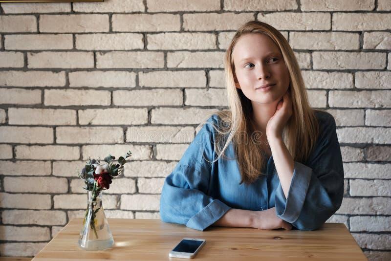 Den unga blondinen i blå skjorta sitter på en tabell i ett kafé som ligger på en telefon royaltyfri bild