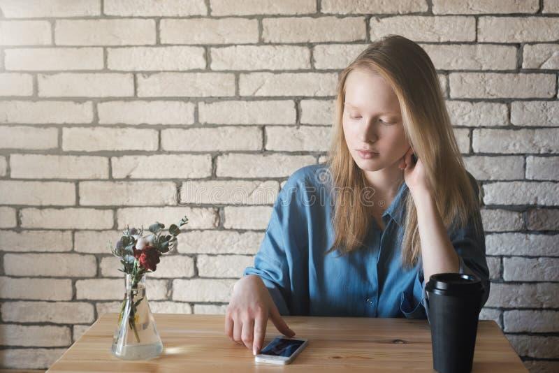 Den unga blondinen i blå skjorta sitter på tabellen i ett kafé på som arkivbilder