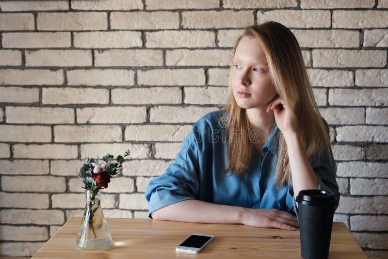 Den unga blondinen i blå skjorta sitter på tabellen i ett kafé på som royaltyfria foton