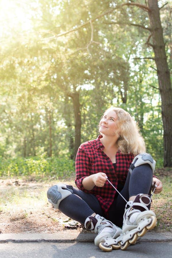 Den unga blongekvinnan binder skosnöre på hennes rullkängor arkivfoto