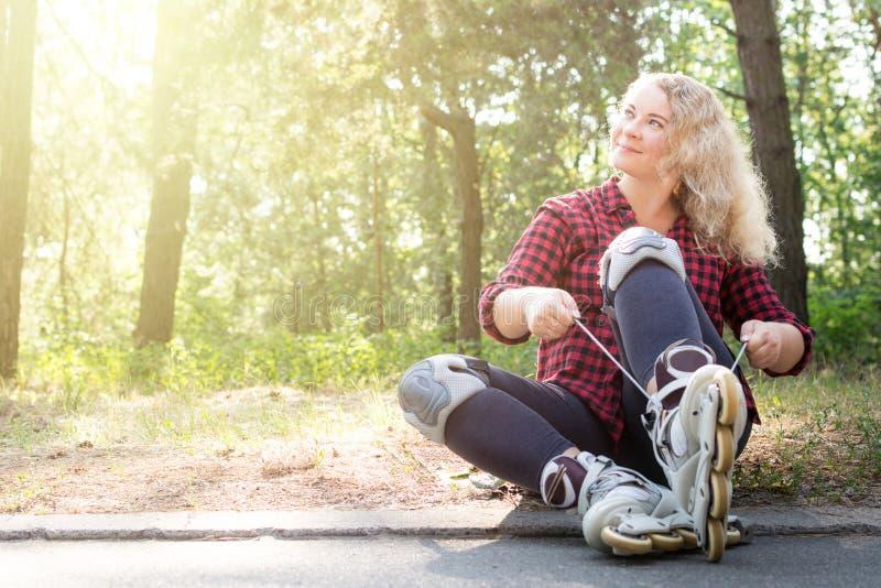 Den unga blongekvinnan binder skosnöre på hennes rullkängor arkivbilder