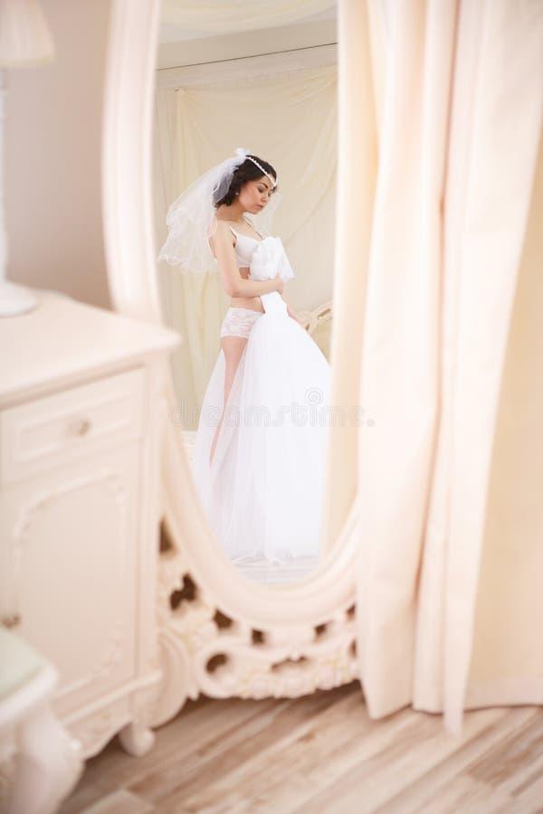 Den unga bruden får klar i den hemmastadda morgonen royaltyfri foto