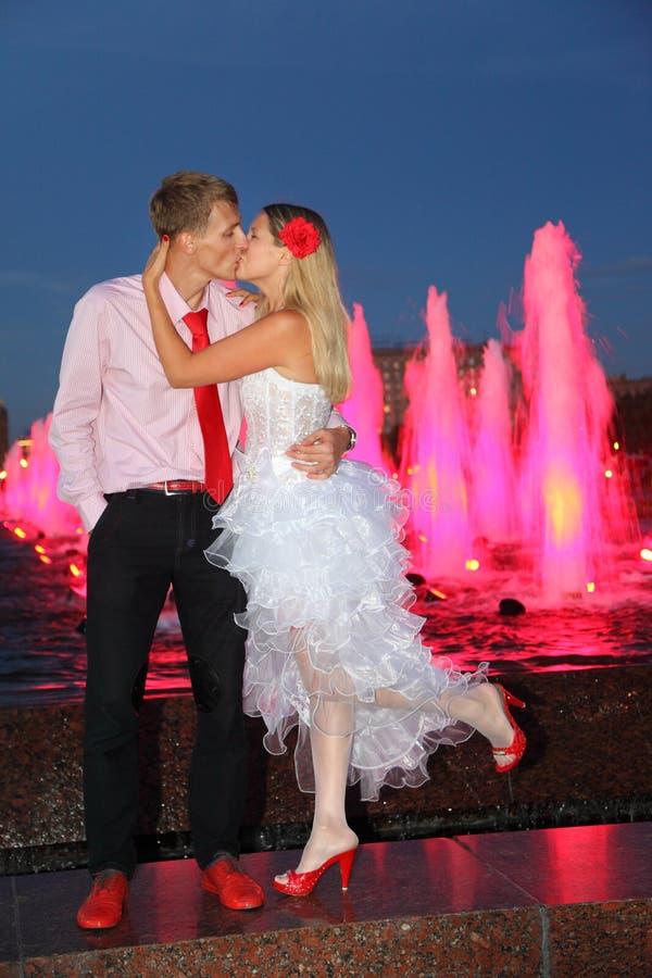 Bruden och brudgummen kysser nära rosa springbrunnar royaltyfri bild