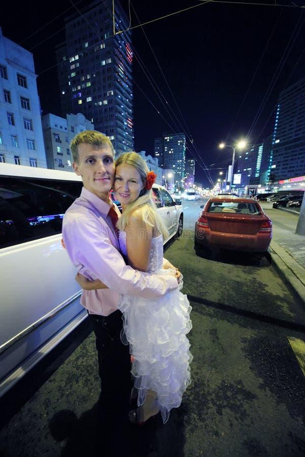 Bruden och brudgummen omfamnar och står nära vitlimousinen fotografering för bildbyråer