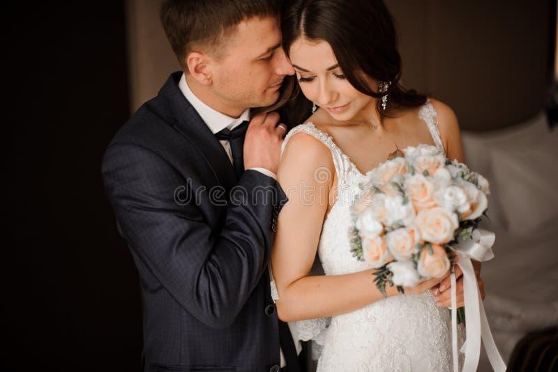 Den unga brudgummen kramar försiktigt hans charmiga brud med en bukett royaltyfri foto