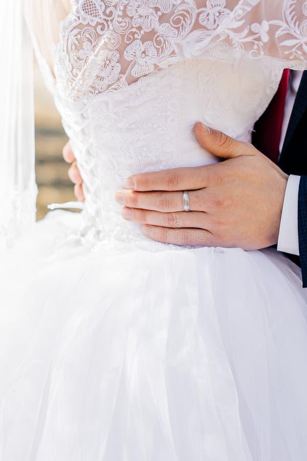 Den unga brudgummen omfamnar bruden royaltyfri fotografi