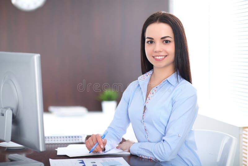 Den unga brunettaffärskvinnan ser som en studentflicka som i regeringsställning arbetar Latinamerikan eller latin - amerikansk fl arkivbilder
