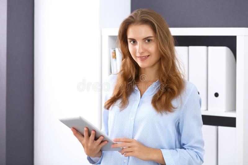 Den unga brunettaffärskvinnan ser som en studentflicka på arbete i regeringsställning Stående raksträcka för flicka med minnestav royaltyfria foton