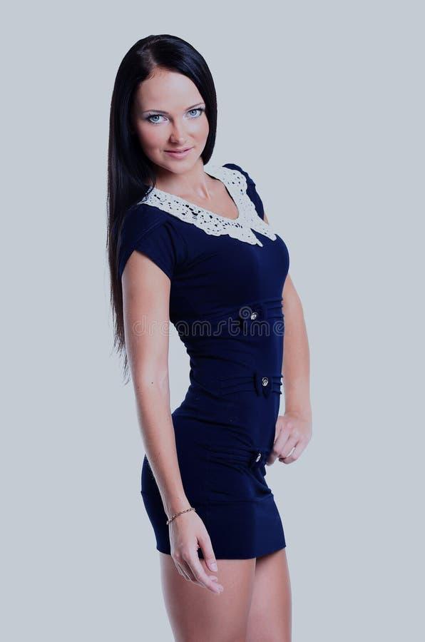 Den unga brunettdamen i blått klär att posera på vit bakgrund royaltyfri fotografi
