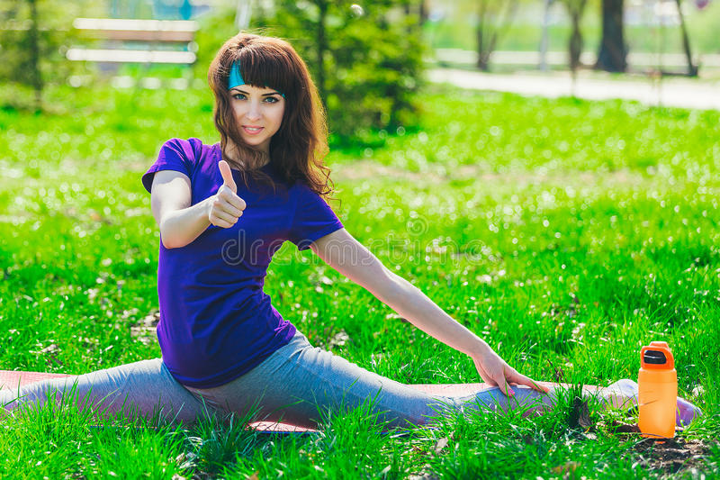 Den unga brunetten i blå sportskjorta på mattt göra för kondition övar utomhus uppvisning av tumen upp kvinna arkivbild