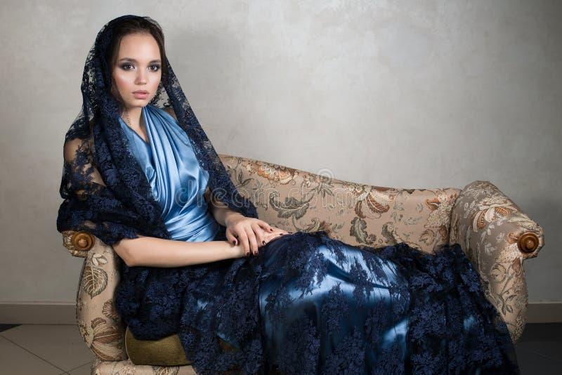 Den unga brunetten i en blå siden- klänning och snör åt mörk udde sitter att luta på armstödtappningsoffan fotografering för bildbyråer