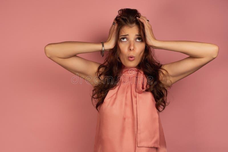 Den unga brunetten rymmer hennes huvud i bryderi med ett roligt framsidauttryck, rosa bakgrund arkivbild
