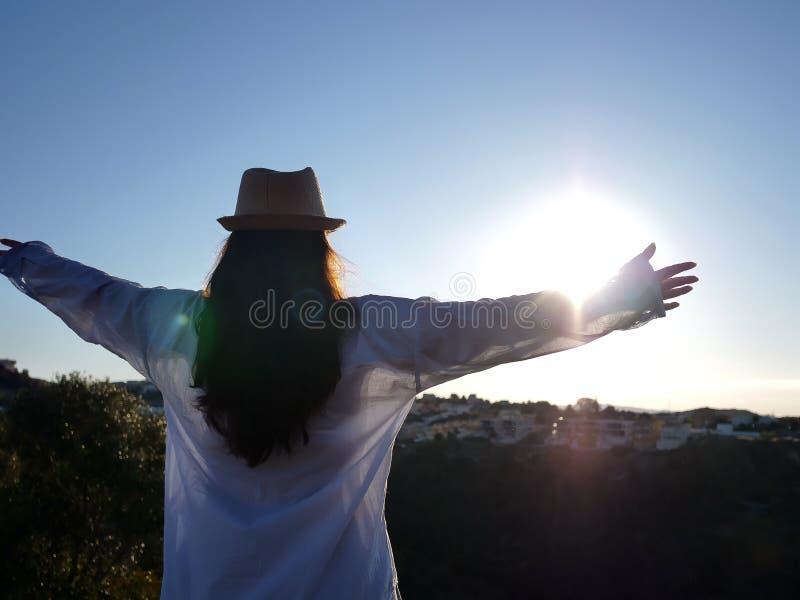 Den unga brunettflickan i en hatt och en blå skjorta möter soluppgången med hennes händer upp, copyspace fotografering för bildbyråer