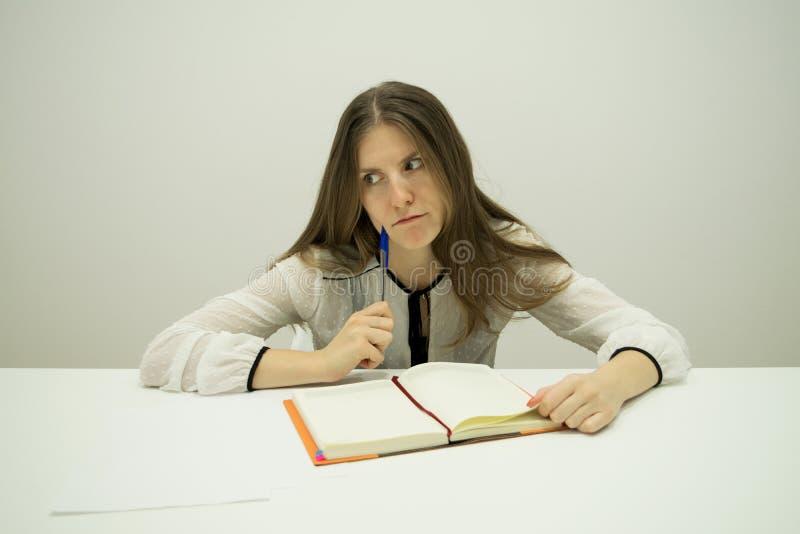 den unga brunettflickan med hennes hår sitter på en tabell med en dagbok på tabellen arkivbild
