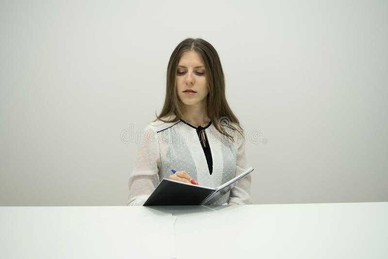 Den unga brunettflickan med hennes raka hår sitter på tabellen med en anteckningsbok i hennes händer royaltyfri foto