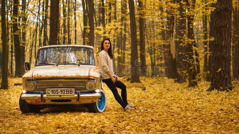 Den unga brunettflickan står nära en retro bil i en höstskog royaltyfri foto