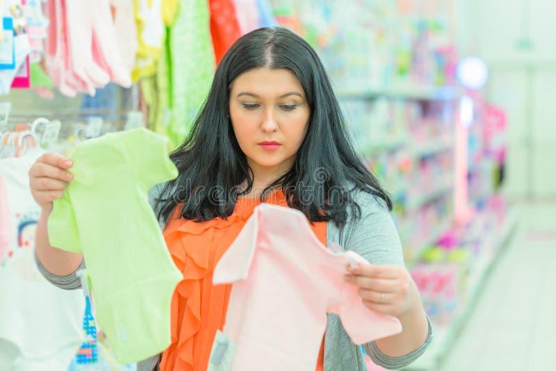 Den unga brunettkvinnamodern som ser och väljer barnskjortor på kläder, shoppar royaltyfria foton
