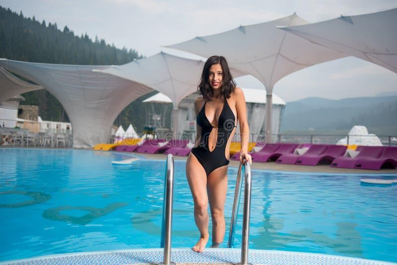 Den unga brunettkvinnan i en sexig baddräkt går ut ur pölen på bergsemesterort royaltyfria foton
