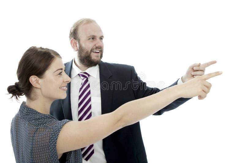 Den unga brunettkvinnan och affärsmannen pekar till vänster arkivfoton