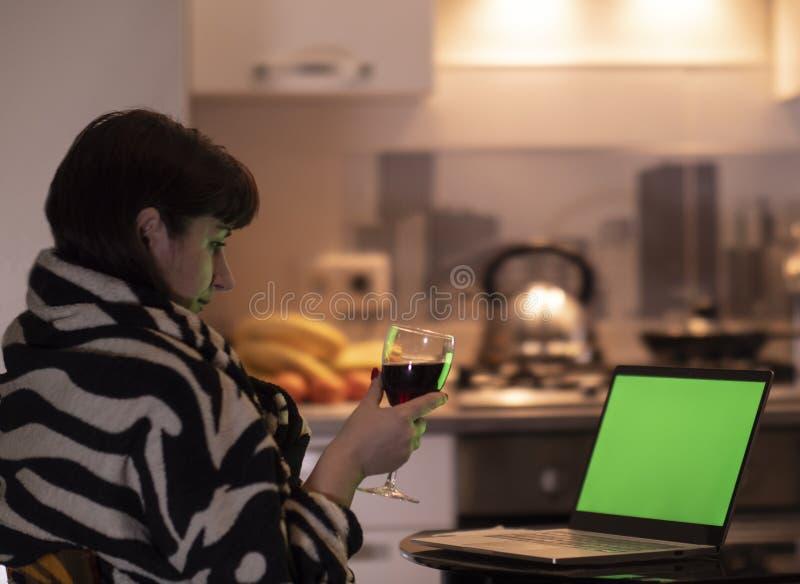 Den unga brunettkvinnan rymmer ett exponeringsglas av alkohol i hennes hand och blickar på skärmen av en bärbar datorbildskärm, c arkivbilder