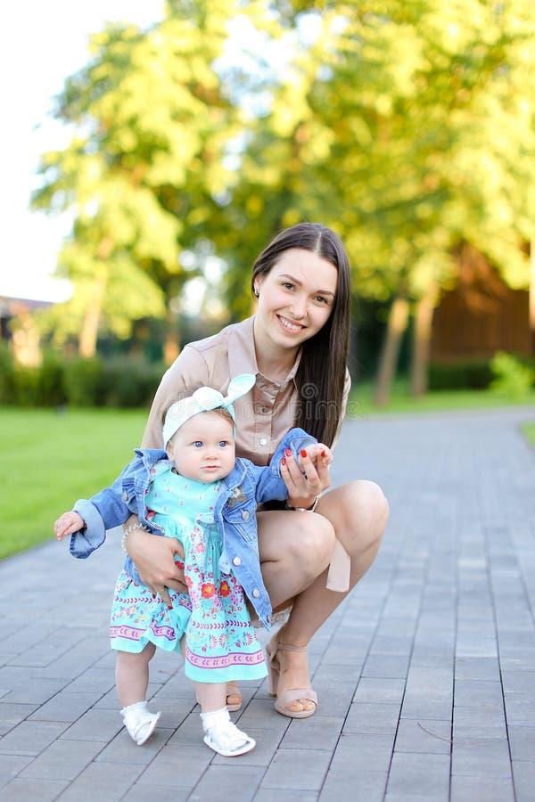 Den unga brunettkvinnan som går med den lilla dottern parkerar in arkivfoto