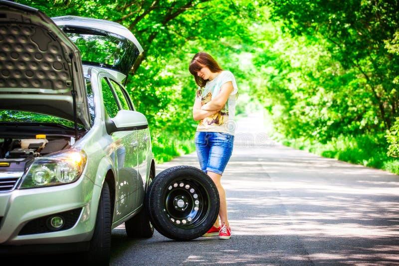 Den unga brunettkvinnan står nära en silverbil på vägrenen med ett brutet hjul arkivbilder