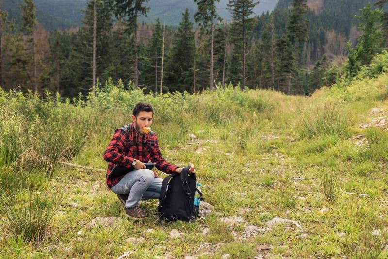 Den unga brunettmannen i jeans och skjorta arbetar på en dator, medan vara på naturen royaltyfri foto