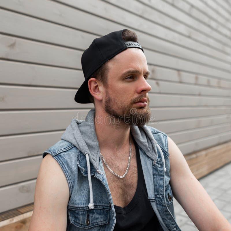 Den unga brutala mannen som hipsteren i ett svart lock i en stilfull grov bomullstvill tilldelar en T-tröja med ett skägg, tycker fotografering för bildbyråer