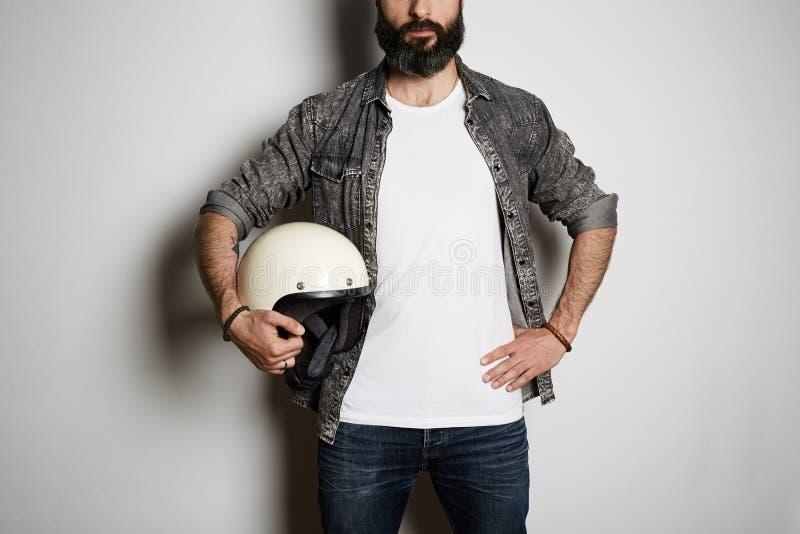 Den unga brutala skäggiga grabben poserar i bomull för sommar för svart jeansskjorta och tom vit t-skjorta högvärdig, på vi fotografering för bildbyråer