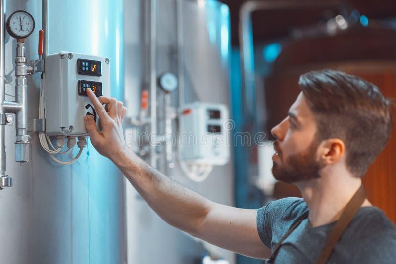 Den unga bryggaren justerar temperaturavkännare på ölbehållare royaltyfria foton