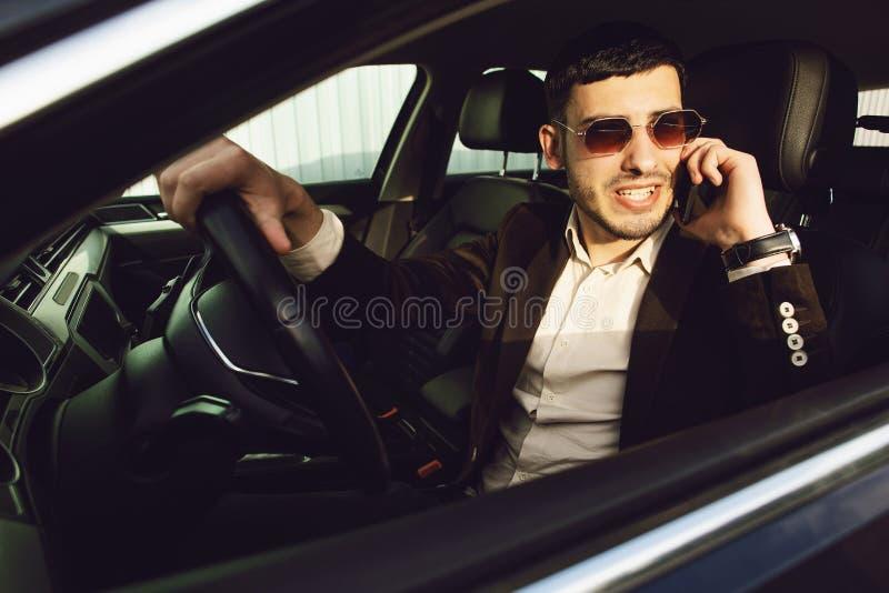 Den unga bussinesmanen i dr?kt och svarta exponeringsglas talar vid telefonen i hans bil r r royaltyfri bild